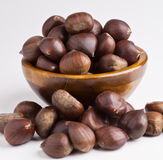 Bowl of chestnuts. Dark wooden bowl with chestnuts. on white royalty free stock photos
