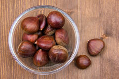 Bowl with chestnuts on wood from above Royalty Free Stock Images