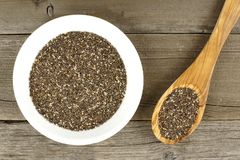 Bowl of chia seeds over wood with spoon Royalty Free Stock Images