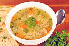 Bowl with chicken soup with vegetables and chicken meat, toasted bread. Spoon, on wooden table Royalty Free Stock Images