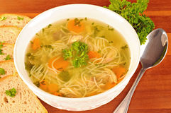 Bowl with chicken soup with vegetables and chicken meat, toasted bread. Spoon, on wooden table Royalty Free Stock Photography