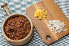 Bowl of chili with cheese and onions on side. Stock Photography