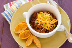 Bowl of chili with chips. A hot bowl of spicy chili with shredded cheese and green onions sprinkled on top sits in a white handled bowl on a green plate with Stock Images
