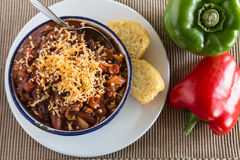 Bowl Chili Corn Bread Muffin With Peppers Eat. Bowl of warm chili winter comfort food dinner with corn bread muffin red and green peppers Stock Photography