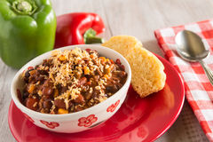 Bowl of Chili With Corn Bread Muffin And Peppers. Bowl of warm chili winter comfort food dinner with corn bread muffin and red and green pepper Royalty Free Stock Images