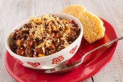 Bowl of Chili With Corn Bread Muffin On Red Plate Stock Photography