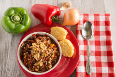 Bowl of Chili With Corn Bread Muffin And Vegetables Above Stock Images