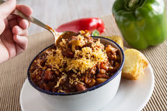 Bowl of Chili With Peppers And Hand Scooping Royalty Free Stock Photos