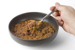 Bowl of chilli and hand holding spoon. Hand holding a spoon into a bowl of chilli isolated over a white background Royalty Free Stock Photos