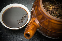 Bowl of Chinese herbal tea and an enamel pot with herbs Royalty Free Stock Images