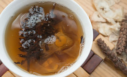 Bowl of Chinese herbal tea with raw herbal Royalty Free Stock Images