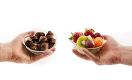 Bowl with chocolates and a bowl of fruit Stock Images