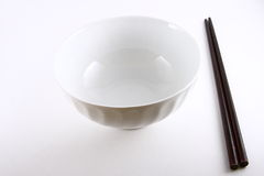 Rice bowl and chopsticks. Empty white rice bowl and chopsticks on studio background stock photos
