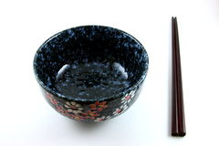 Japanese bowl and chopsticks. Empty flowery Japanese bowl and chopsticks on white background royalty free stock photos