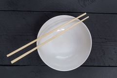 Bowl with chopsticks on a black wooden bird's eye view Stock Images