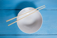 Bowl with chopsticks on a blue wooden bird's eye view Royalty Free Stock Image