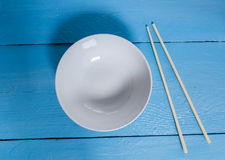 Bowl with chopsticks on a blue wooden bird's eye view Stock Photography
