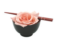 Bowl, chopsticks and rose. Large pink rose in Asian style bowl with chopsticks Royalty Free Stock Image