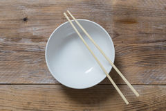 Bowl with chopsticks on wooden bird's eye view Royalty Free Stock Photo