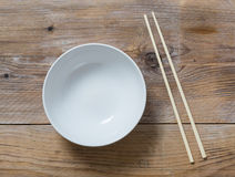 Bowl with chopsticks on wooden bird's eye view Royalty Free Stock Images
