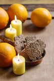 Bowl of christmas cookies among aromatic oranges and yellow cand Royalty Free Stock Photo