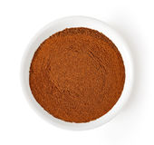 Bowl of cinnamon powder isolated on white, from above Royalty Free Stock Images