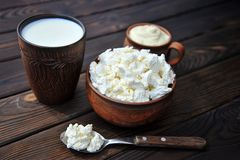 A bowl of clay with cottage cheese, a mug of clay with sour cream, a mug with milk and a spoon on a table royalty free stock photo