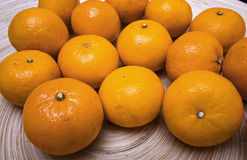 Bowl of clementines. Wooden flat dish with large juicy clementines Stock Photography