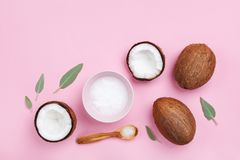 Bowl with coconut oil and fresh half of coconuts on pink table top view. Beauty and spa homemade cosmetic. Flat lay. Bowl with coconut oil and fresh half of stock image
