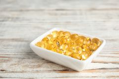 Bowl with cod liver oil pills. On wooden background, closeup royalty free stock photo