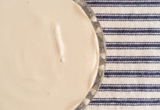 Bowl of coffee flavored yogurt on a striped tablecloth Stock Photos