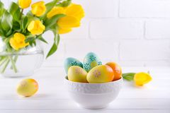 Bowl with colorful Easter eggs, spring easter decoration on white wooden table with bouquet of yellow tulip flowers in glass vase. On white background. Easter royalty free stock images