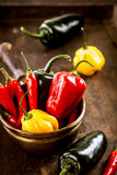 Bowl of colorful fresh chili and sweet peppers. Bowl of colorful fresh cayenne chili peppers and red and yellow sweet peppers with fresh eggplant or aubergine on Stock Photography