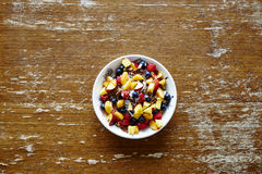 Bowl of colorful healthy cereal with fruit on vintage table Royalty Free Stock Image