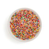 Bowl with colorful sugar sprinkle dots. decoration for cake and pastry. Top view. Isolated on white.  royalty free stock photos