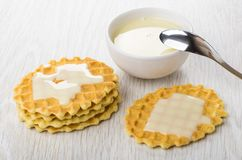 Bowl with condensed milk and milk on wafer cookies, teaspoon. On wooden table Stock Images