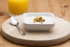 Bowl of conflakes yogurt and orange juice Royalty Free Stock Image