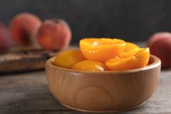 Bowl with conserved peach halves on wooden table. Space for text stock image