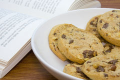 Bowl of cookies and book. A bowl of chocolate chips cookies with a book Stock Photography