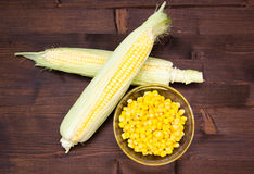 Bowl of corn cobs and wood on top Stock Photo