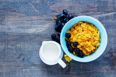 Bowl of corn flakes. Breakfast theme table with bowl of corn flakes, milk, grapes and fresh blackberries on vintage wooden background. Top view. With copy space Stock Photography