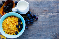 Bowl of corn flakes. Colorful breakfast theme table with bowl of corn flakes, milk, grapes and fresh blackberries on vintage wooden background. Top view. With Royalty Free Stock Photography