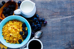 Bowl of corn flakes. Healthy breakfast theme table with bowl of corn flakes, coffee cup, milk, grapes and fresh blackberries on vintage wooden background. Top Royalty Free Stock Photography