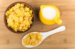 Bowl with corn flakes, jug of milk and plastic spoon Stock Photography