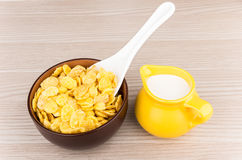 Bowl with corn flakes and jug of milk on table Stock Photo