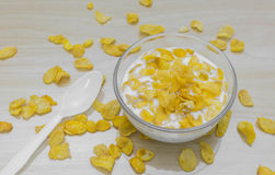 Bowl of corn flakes and spoon on wood background. Bowl of corn flakes and spoon beside bowl on wood background Stock Image