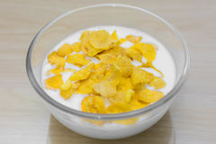 Bowl of corn flakes and on wood background for morning breakfast. Yellow corn flakes on wood background for morning breakfast Stock Photos