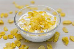 Bowl of corn flakes and on wood background. Bowl of corn flakes, spread cornflakes on wood background Stock Photos