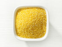 Bowl of corn grains. Bowl of ground corn grains on white wooden table Stock Images