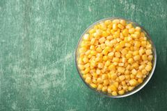 Bowl with corn kernels on green wooden background, top view. Space for text royalty free stock image